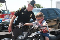 oklahoma highway patrolman standing next to a child who is sitting on an atv