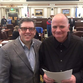 two men smiling and standing together on the oklahoma senate floor