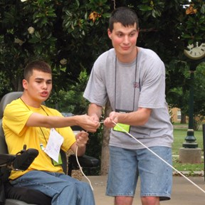 two people, one in a wheelchair and the other standing, together pulling on a string